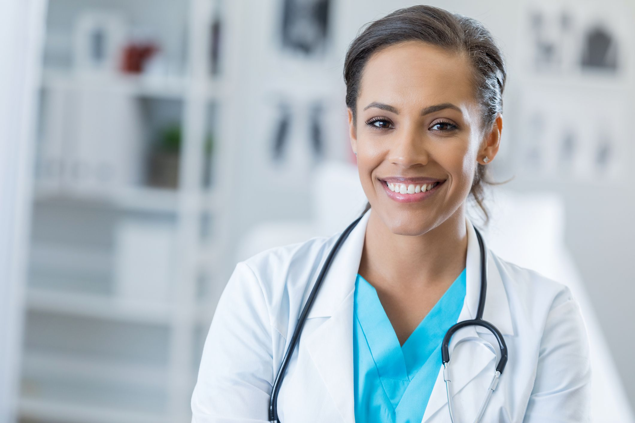 Pretty mid adult African American surgeon smiles cheerfully at the camera. She is wearing a stethoscope and lab coat.