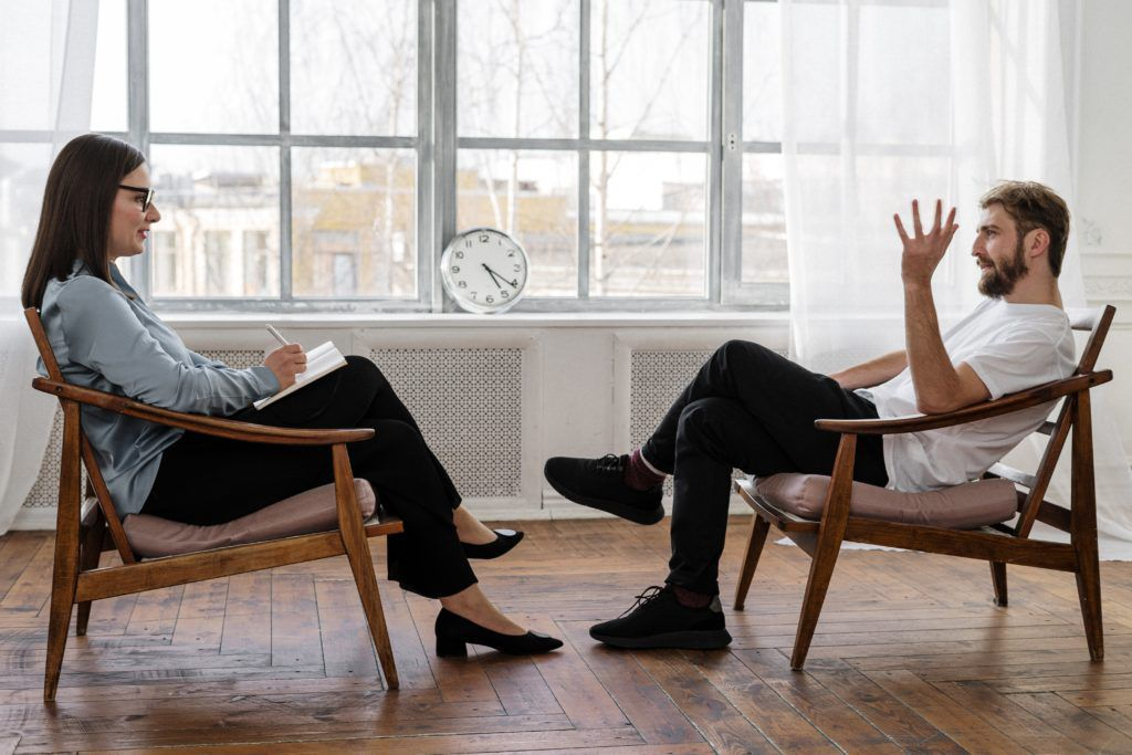A woman therapist talking to her male client in a office.