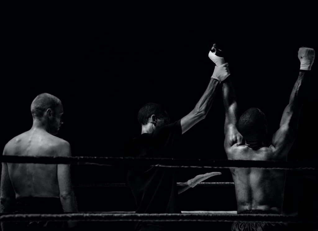 2 men in a boxing ring with the referee declaring one the men, the winner