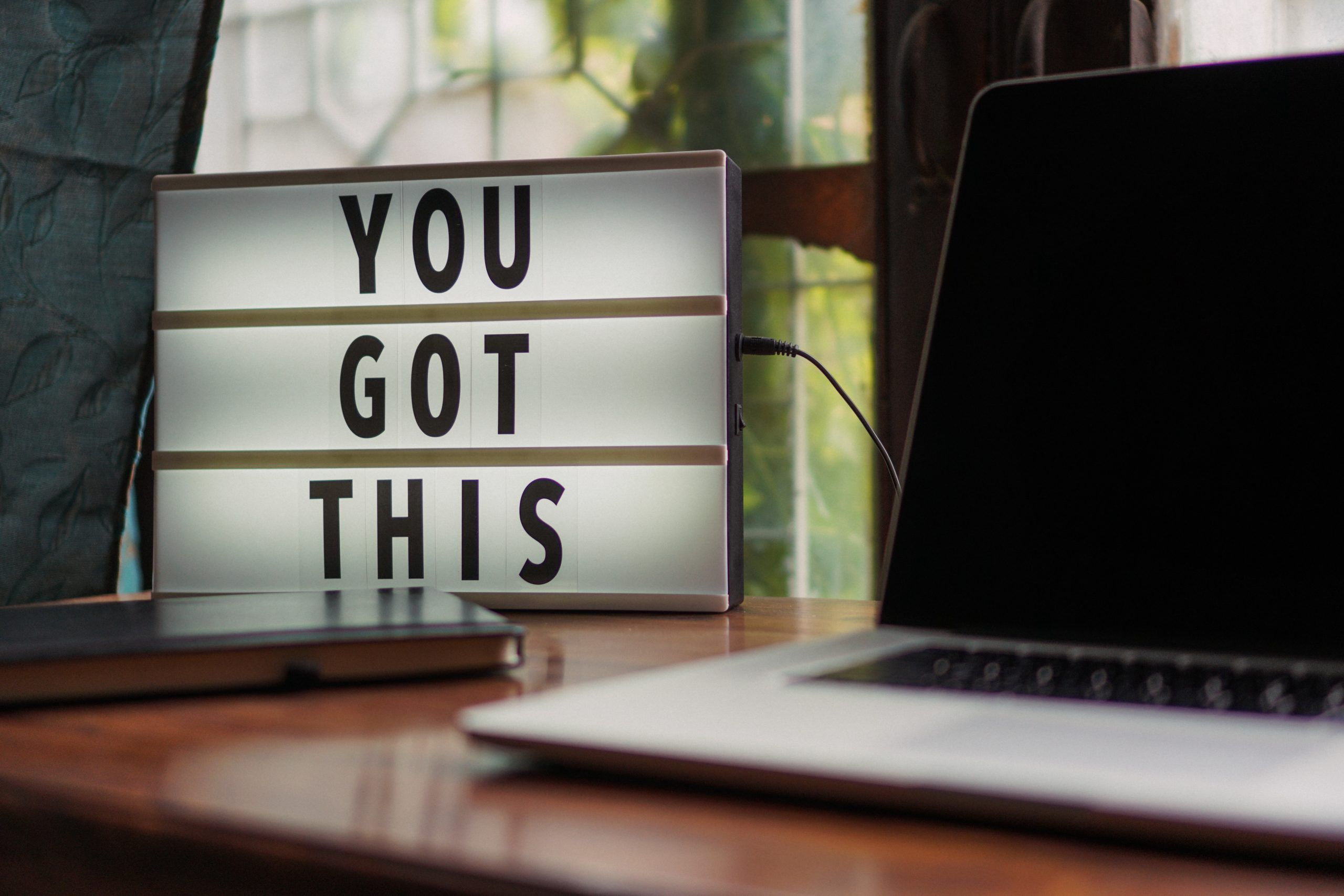 """A desktop sign that says """"You Got This"""" next to a laptop"""