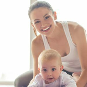 Portrait of beautiful young mom in sports wear looking at camera and smiling while working out with her charming little baby on yoga mat against window