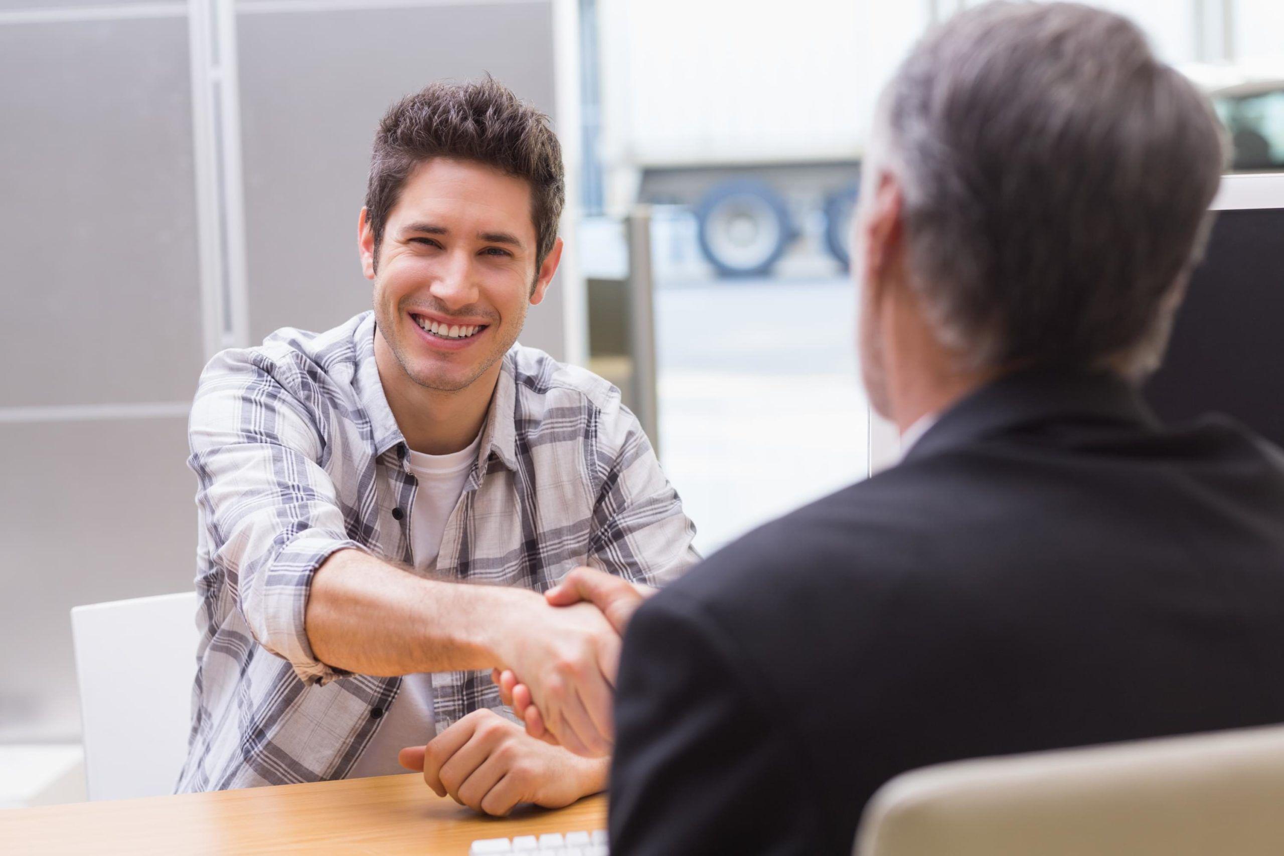 Smiling customer shaking a salesman hand at new car showroom