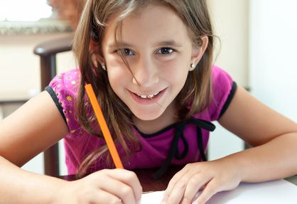 Beautiful small girl smiling at the camera and working on her school project at home